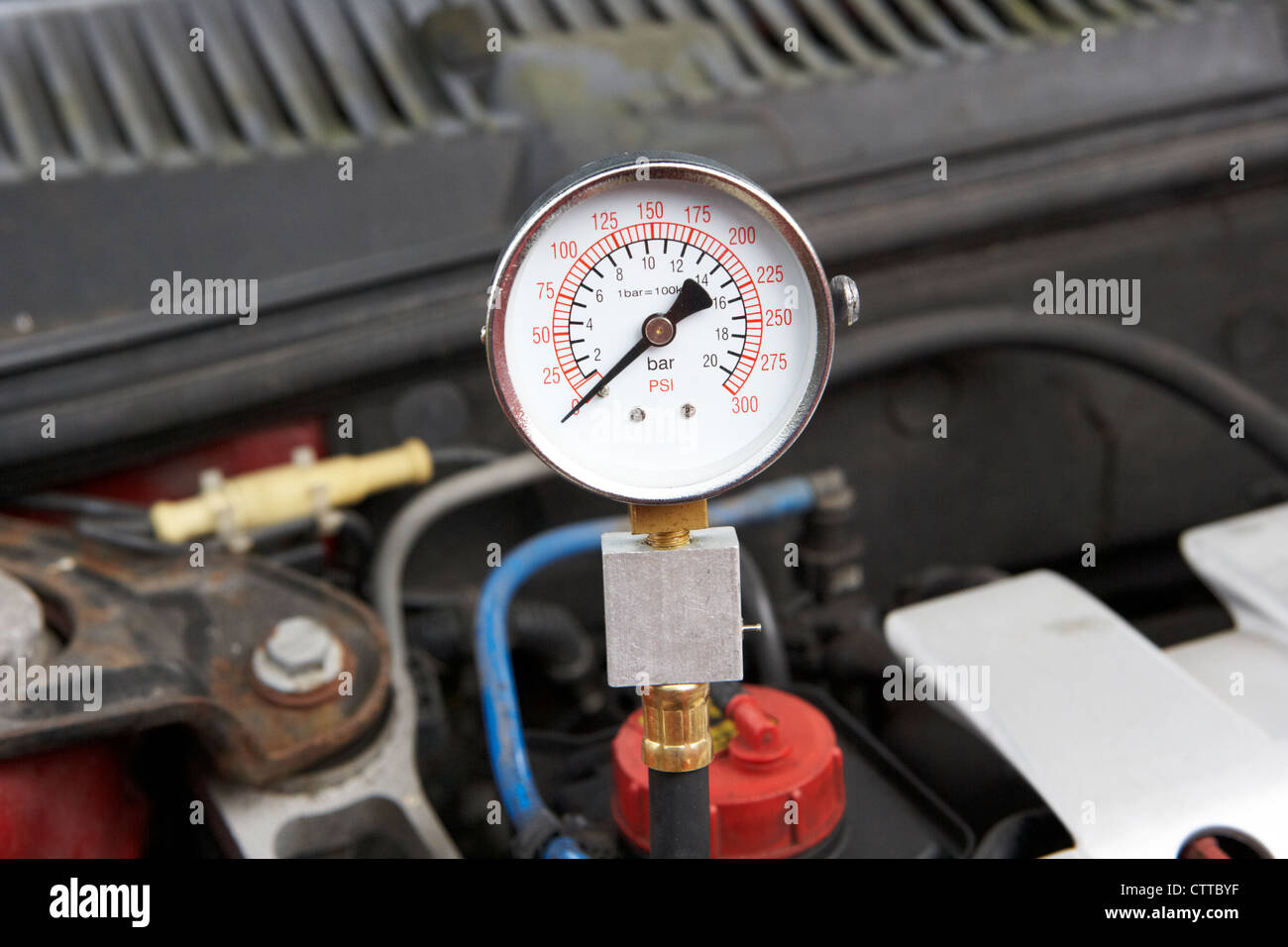 using a compression tester to measure the compression on a car engine cylinder showing zero reading - Stock Image