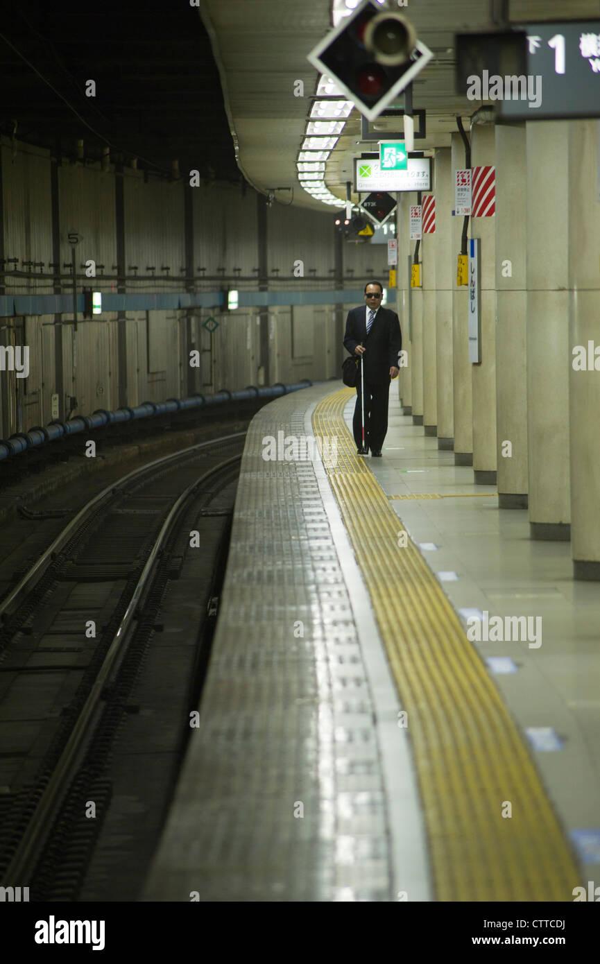 Blind man on a JR train platform in Tokyo - Stock Image