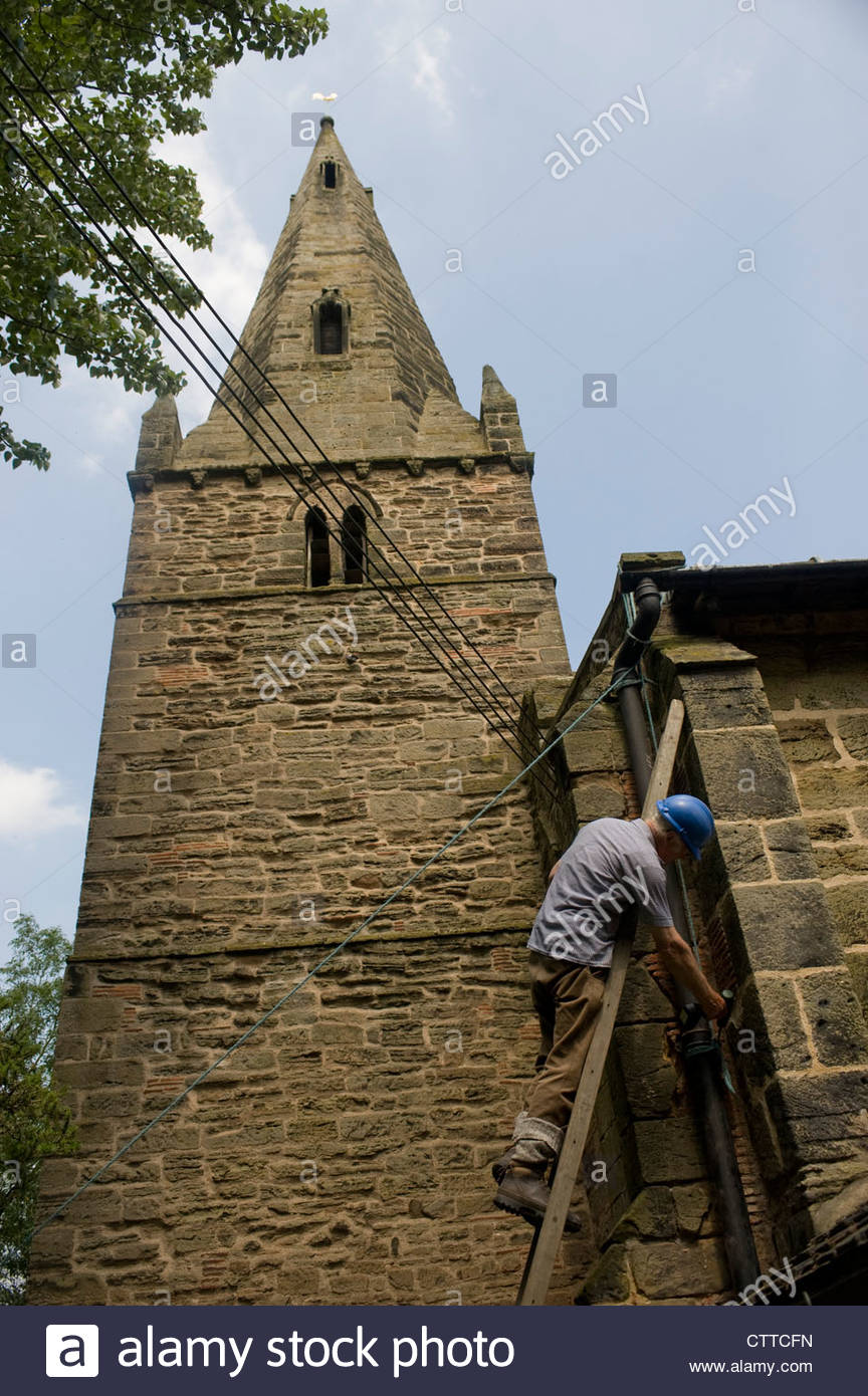 Workman on a ladder repairing a church drainpipe. - Stock Image