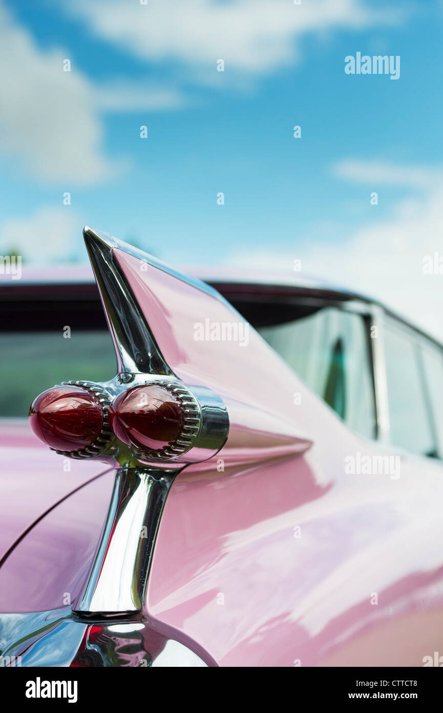 1959 Pink Cadillac. Sharp tail fin with dual bullet tail lights - Stock Image