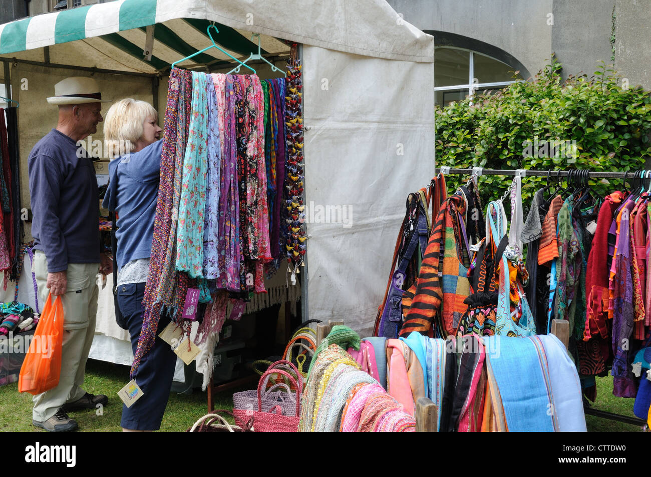 A woman buying a fair trade clothes from a stall at a country fair Ceredigion Wales Cymru UK GB - Stock Image