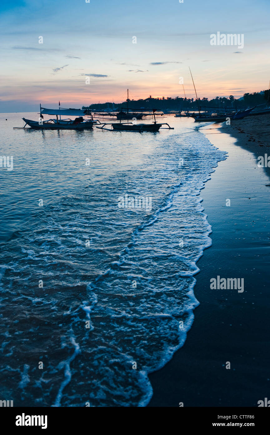 Fishing boats, called jukung, are anchored off the beach in Pemuteran, Bali during a beautiful sunrise. - Stock Image