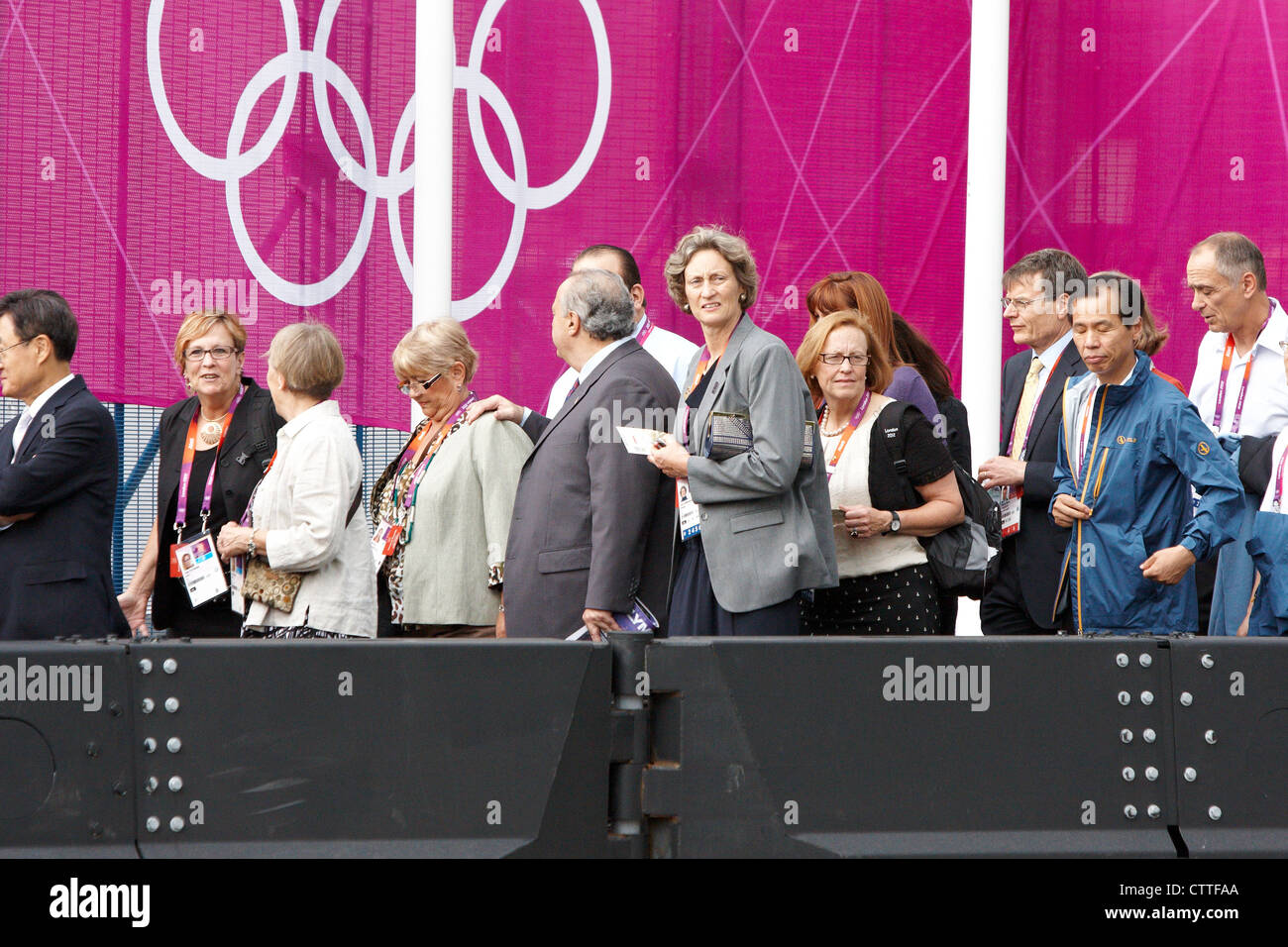 IOC Olympic delegates queue outside the Hilton Hotel for buses to take them to the Olympic Stadium - Stock Image