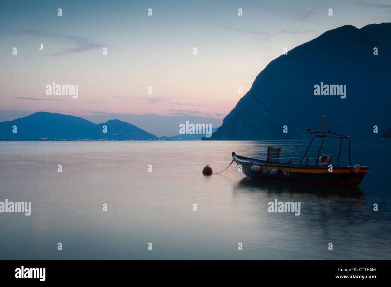 Lake Iseo from Peschiera, Monte Isola, Italy, at night with mountains, crescent moon, distant lights and boat. - Stock Image