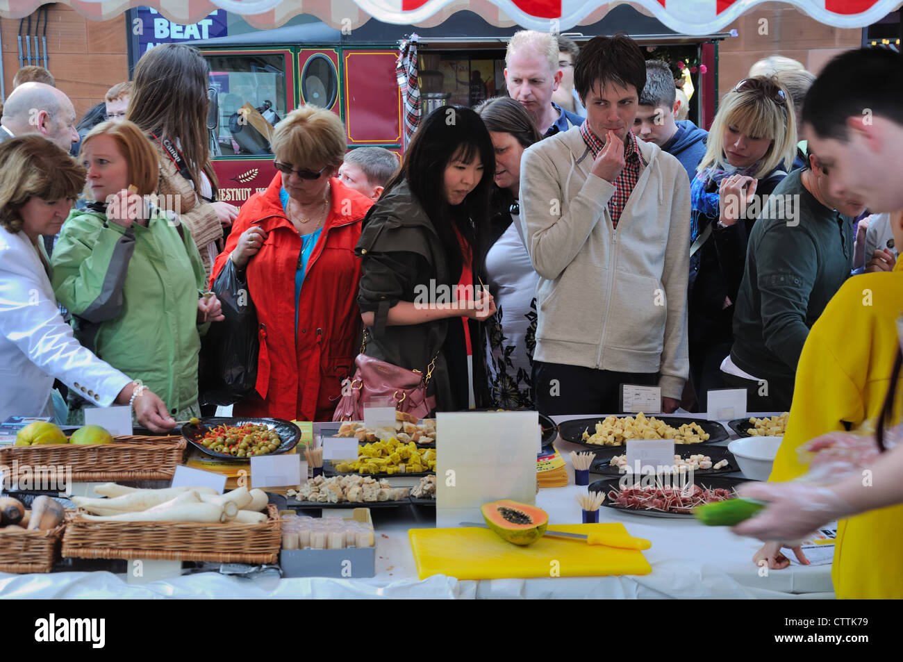 People gathered round a stall and sampling finger food at the Merchant city festival, Glasgow, Scotland, UK. - Stock Image