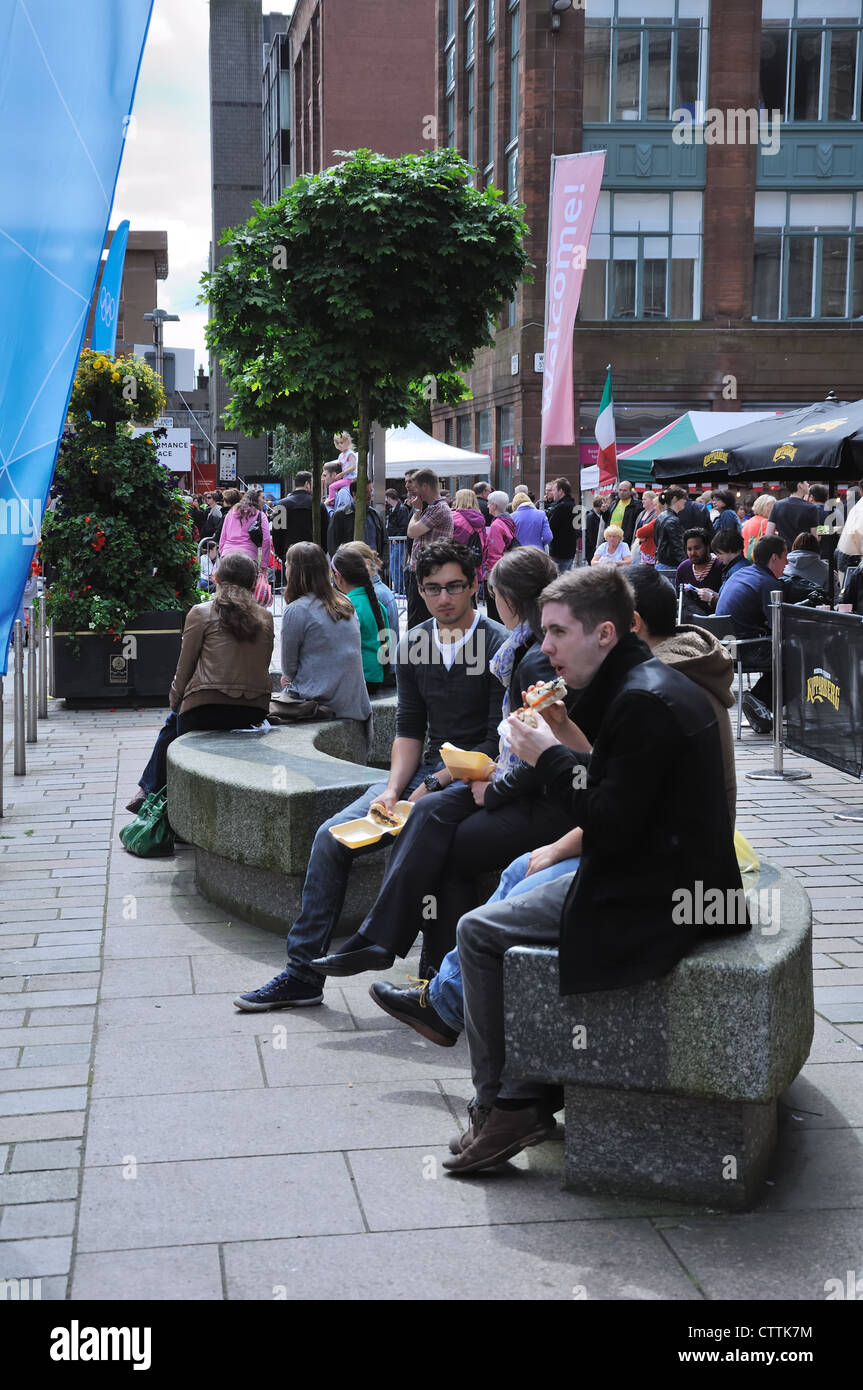 People sitting having a snack at the Merchant City Festival in Glasgow - Stock Image