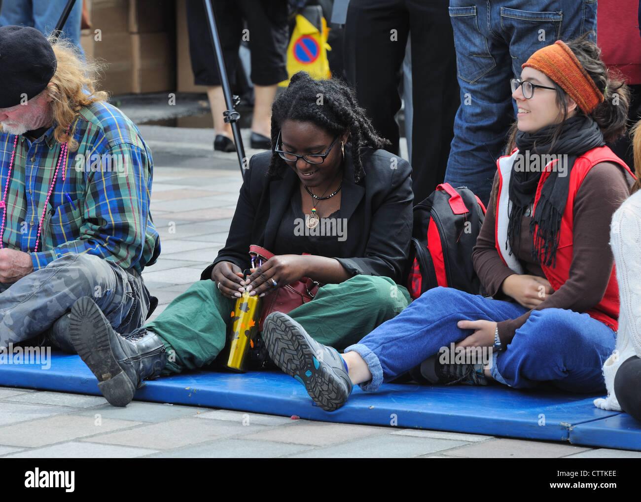 Spectators wait for street performance at the Merchant City Festival. - Stock Image