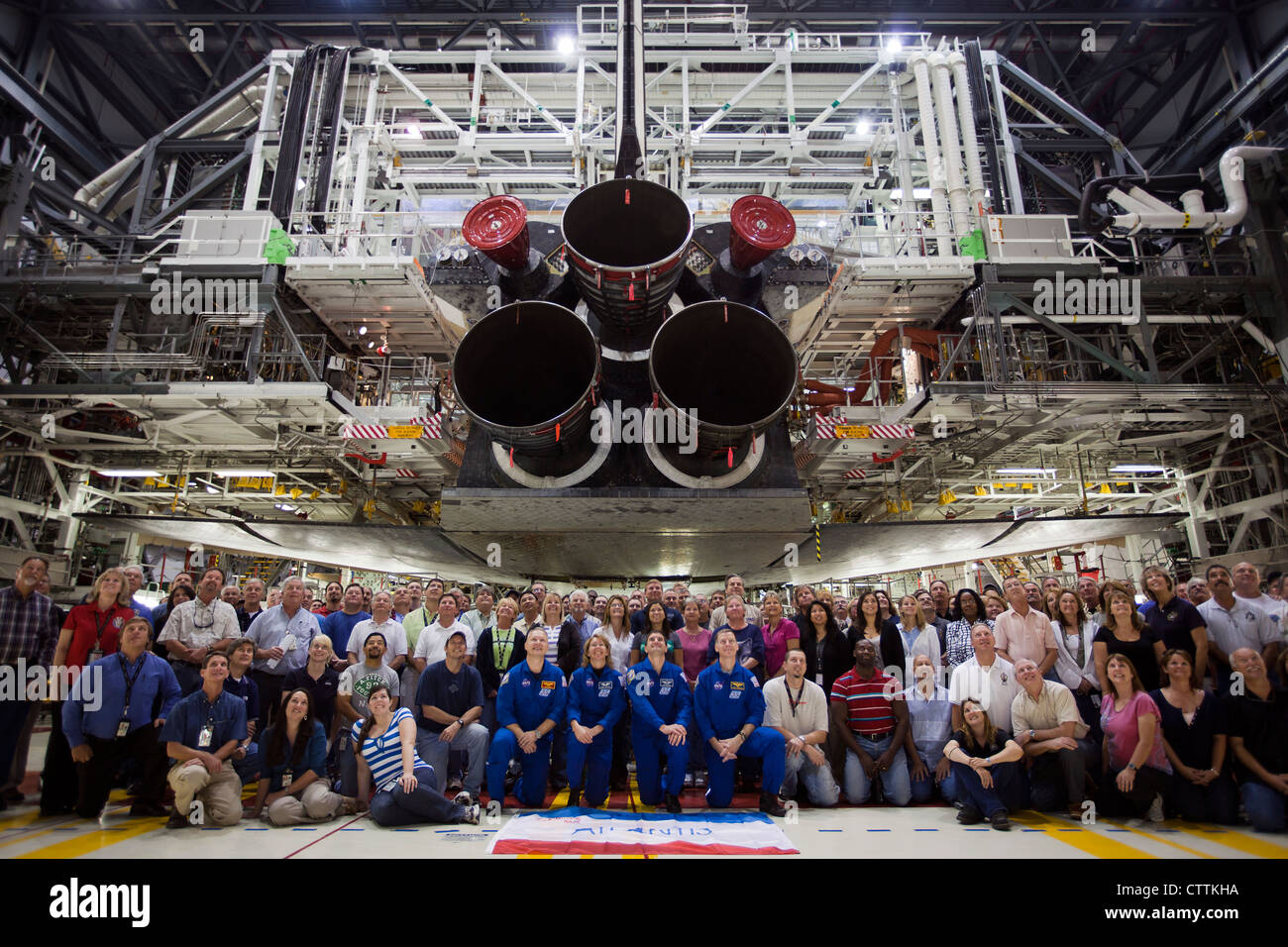 The STS-135 crew members pose for a group photo under the space shuttle Atlantis in the Orbiter Processing Facility - Stock Image