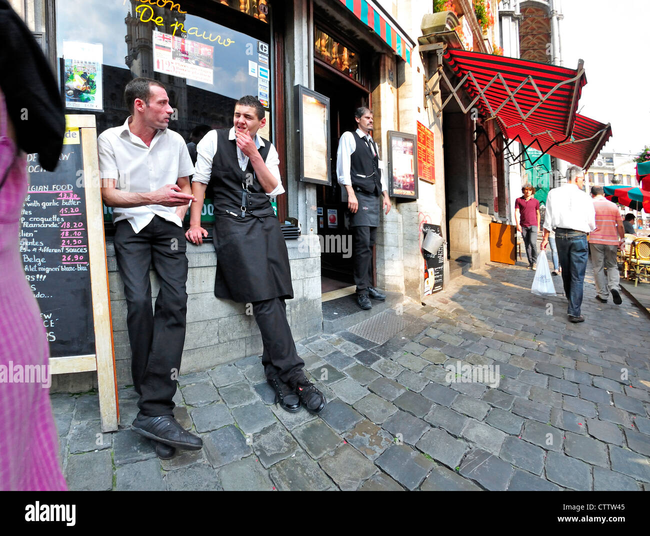 Brussels, Belgium. Waiters relaxing outside restaurant - Stock Image