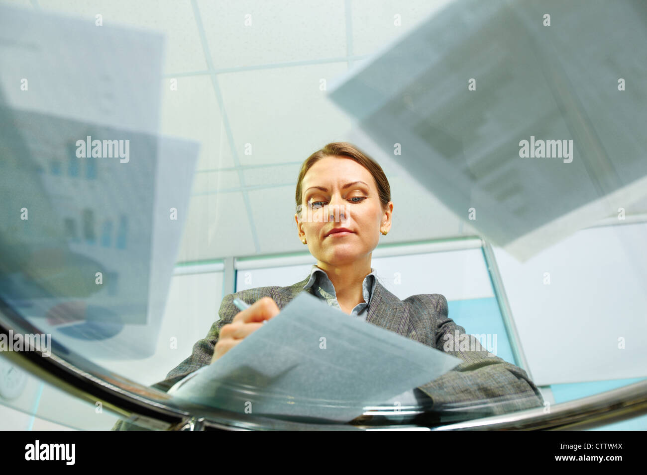 Business woman viewed from below signing documents and working with papers - Stock Image