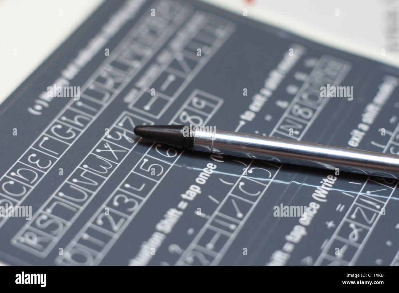 pda stylus on handwriting guide - Stock Image