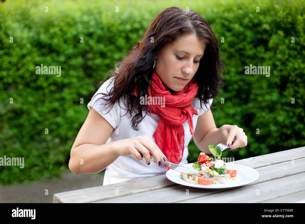 Portrait of a woman with a red scarf seriously eating her meal outdoors Stock Photo