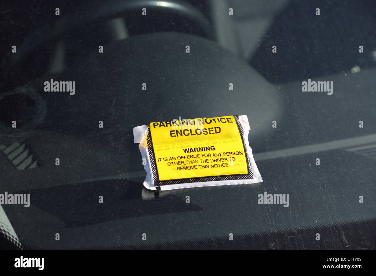 A parking violation notice has been placed onto a cars dirty windscreen. - Stock Image