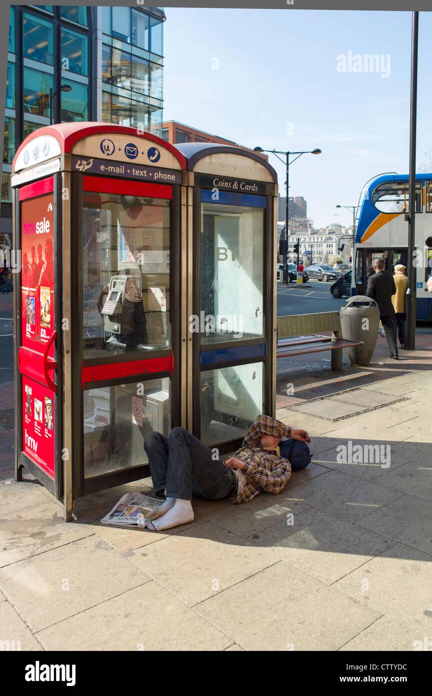Man sleeping by a telephone Kiosk - Stock Image
