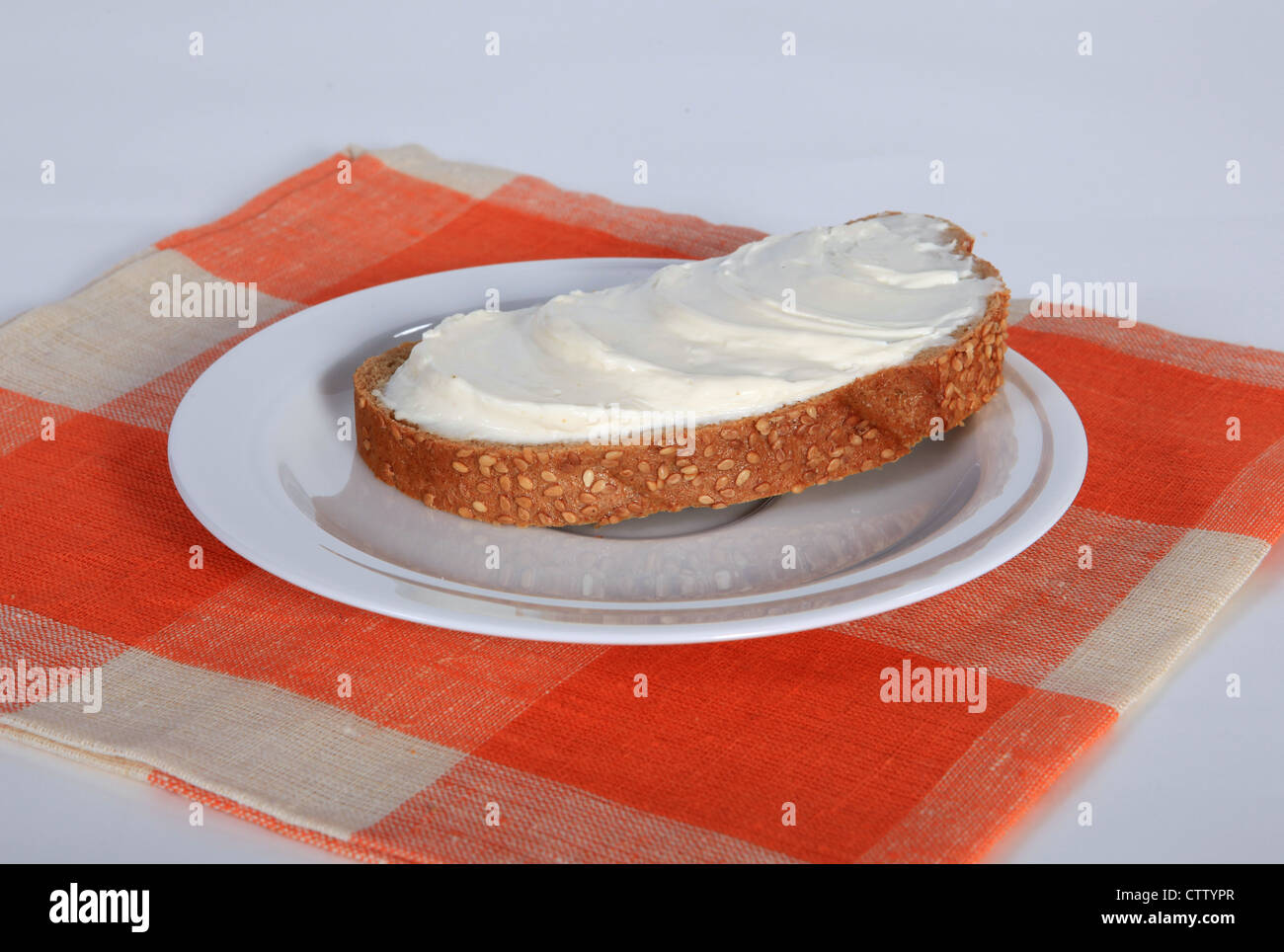Appetizing sandwich with butter on the white saucer - Stock Image