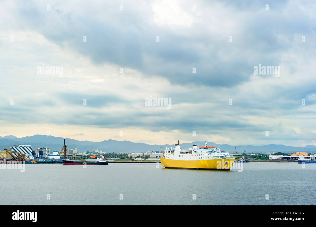 Yellow ship in industrial harbor. Cebu, Philippines - Stock Image