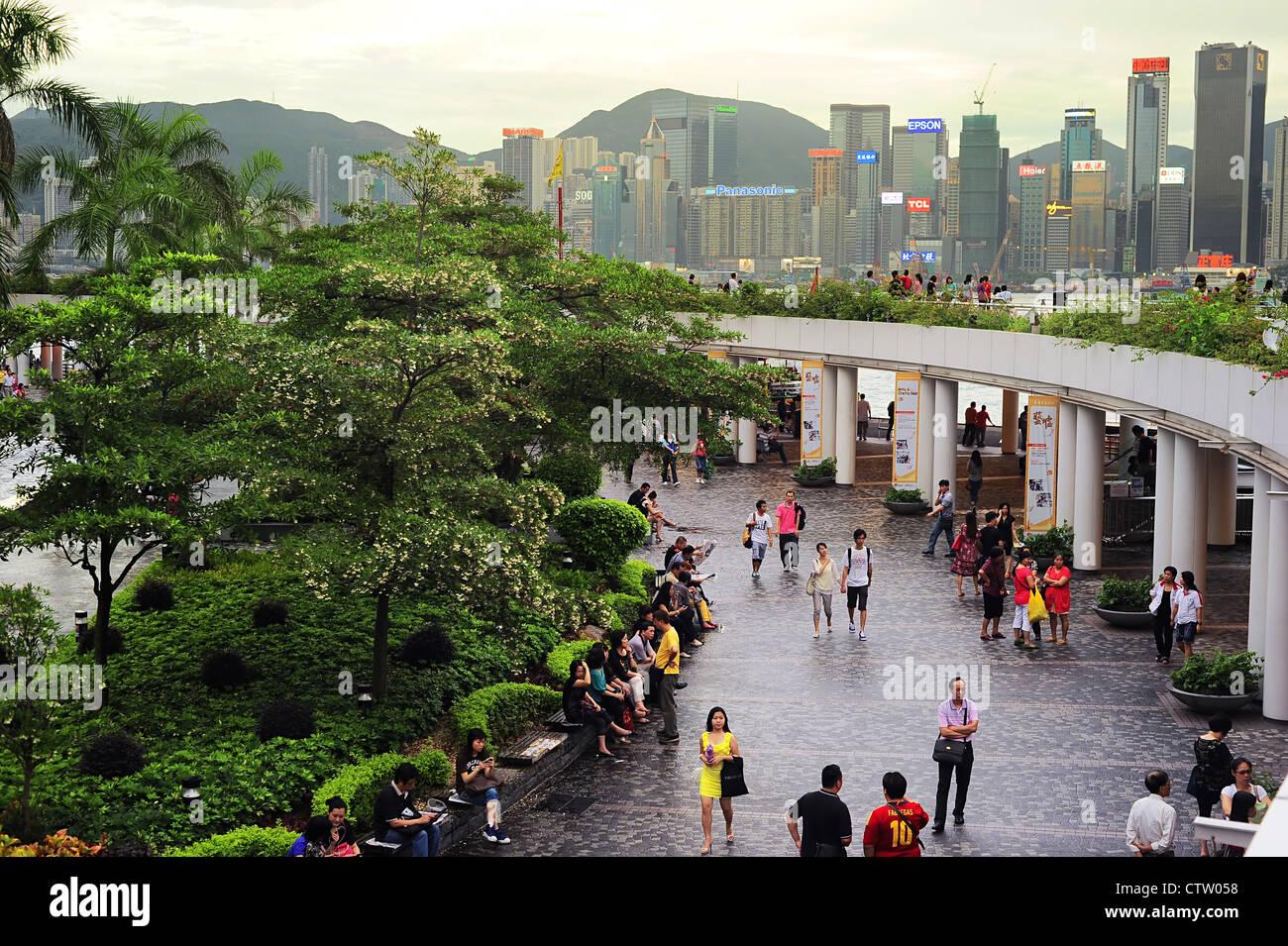 People at Tsim Sha Tsui at sunset. - Stock Image