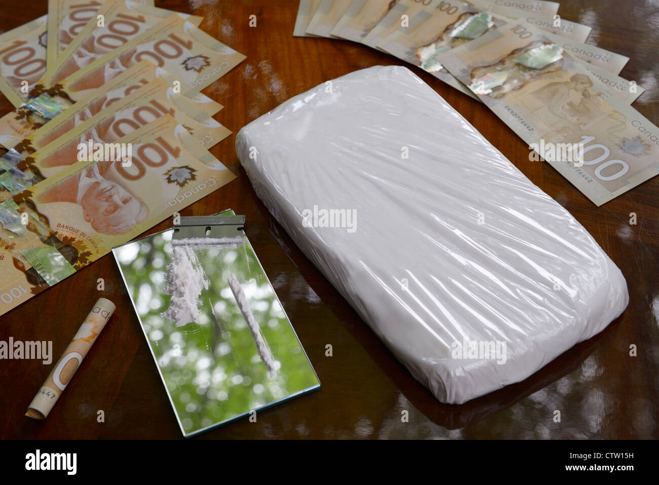 Large bag of cocaine and coke line with razor blade on mirror on table with Canadian 100 dollar bills cash money - Stock Image