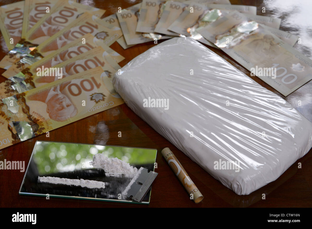 Fanned out Canadian 100 dollar bills with bag of cocaine and coke line with razor blade on mirror - Stock Image