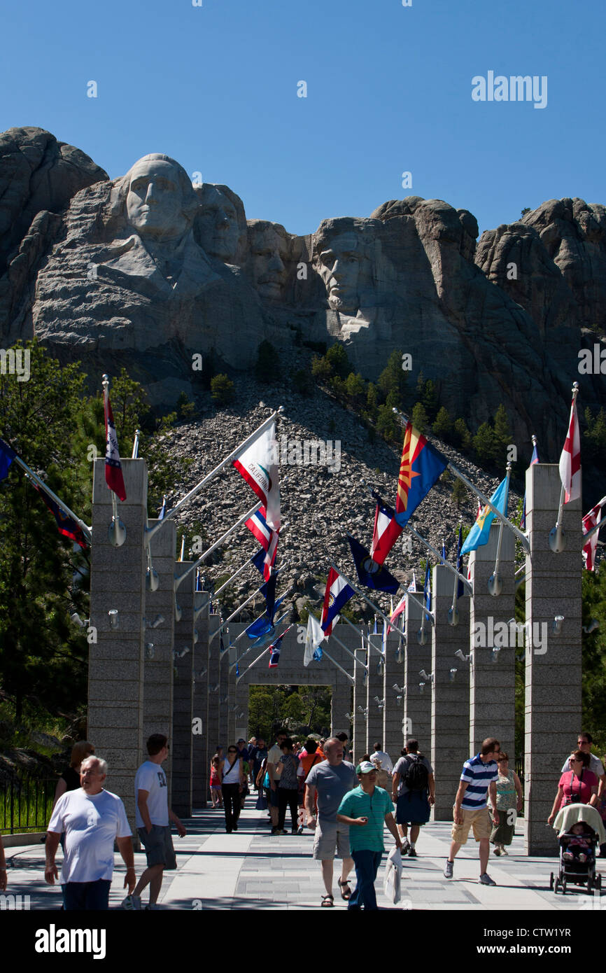 View of Mt. Rushmore with visitors walking along flags of the United States, Mount Rushmore National Monument, South Stock Photo