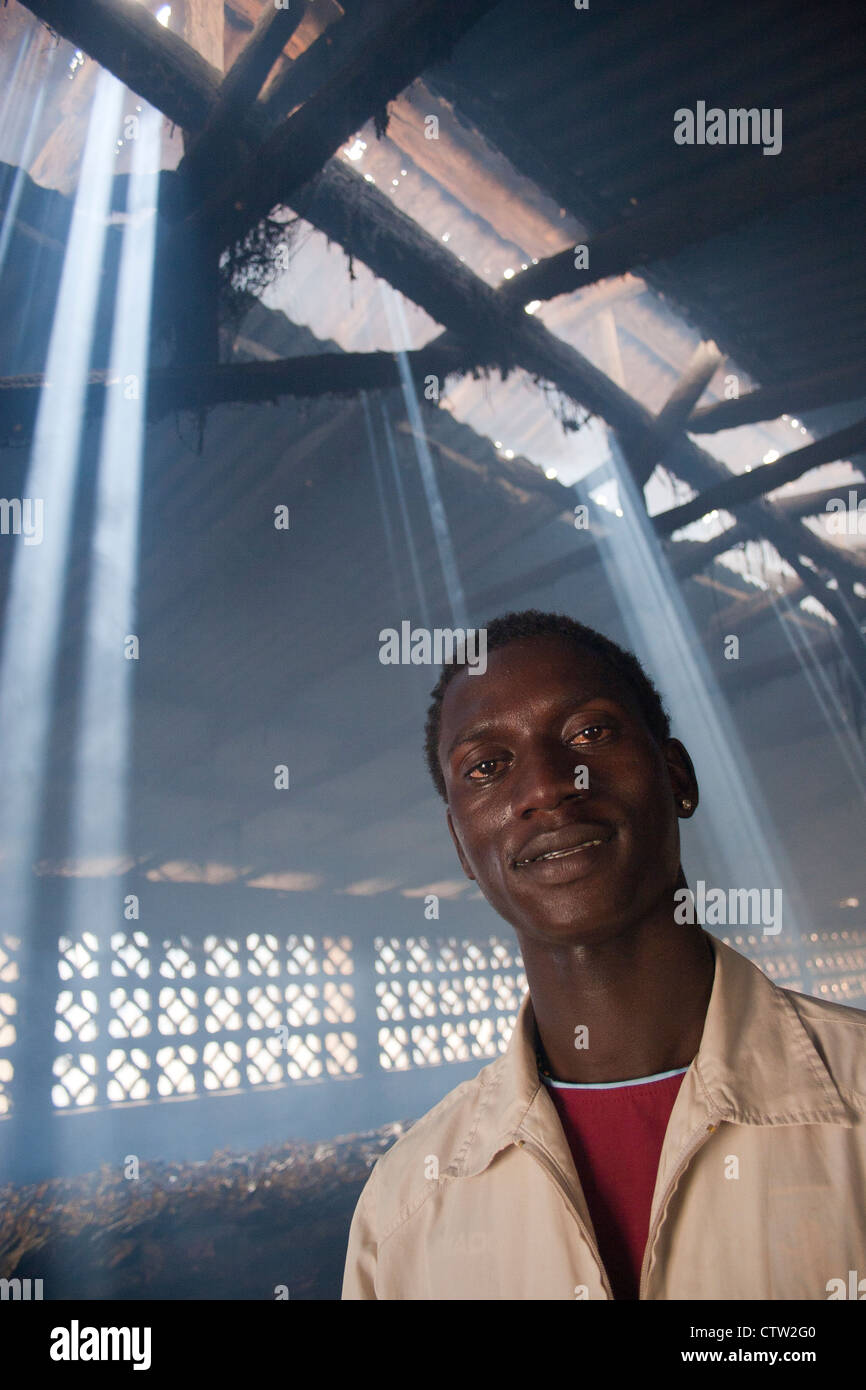 Portrait of man in fish smokehouse, The Gambia, Africa. - Stock Image