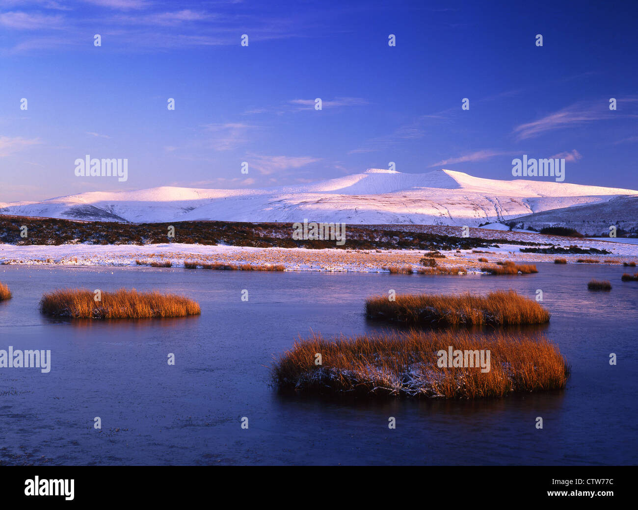 Brecon Beacons in snow Pen y Fan and Corn Du from Traeth Mawr, Mynydd Illtyd at sunset Winter Powys South Wales - Stock Image