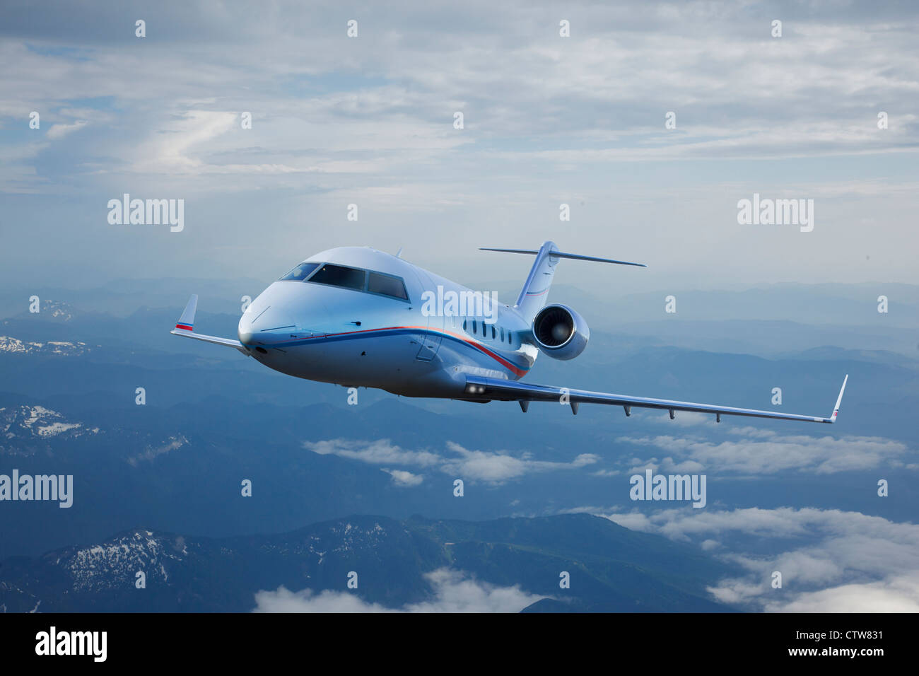 A Bombardier Challenger 601 clears hazy mountains. - Stock Image