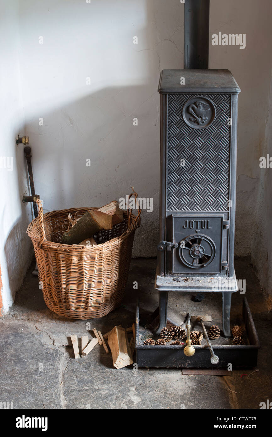 Woodburning stove and a basket of logs in the front room of an english cottage. UK Stock Photo
