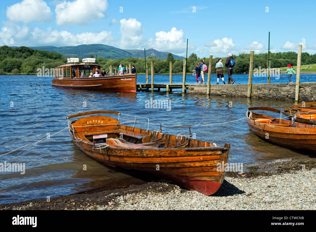Tourists on a ferry with rowing boats in the foreground on Derwentwater, Keswick in the Lake District, Cumbria Stock Photo