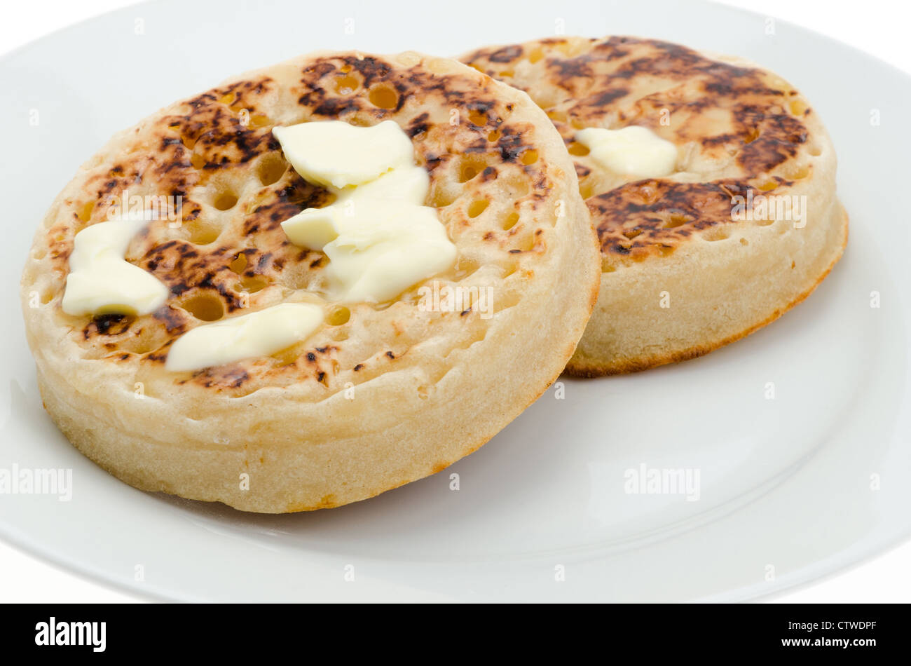 Two hot crumpets with melting butter - studio shot with a shallow depth of field and a white background - Stock Image