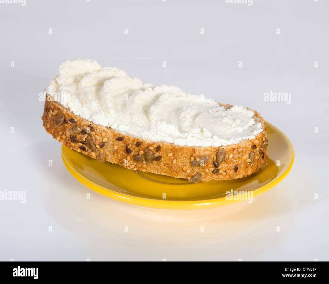 Appetizing sandwich with butter on the yellow saucer - Stock Image