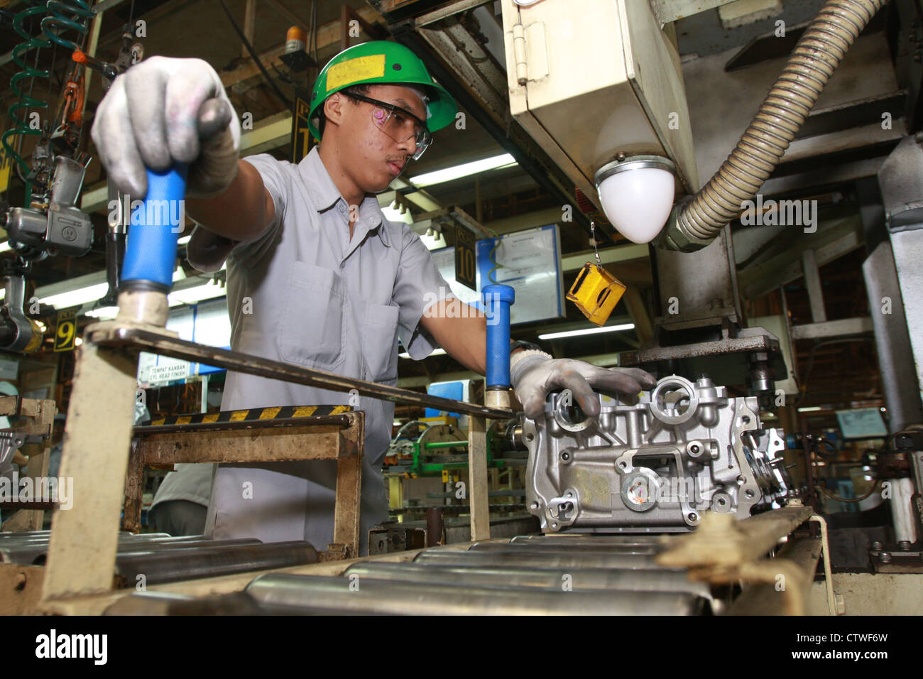 A worker assemble the machine in a factory - Stock Image