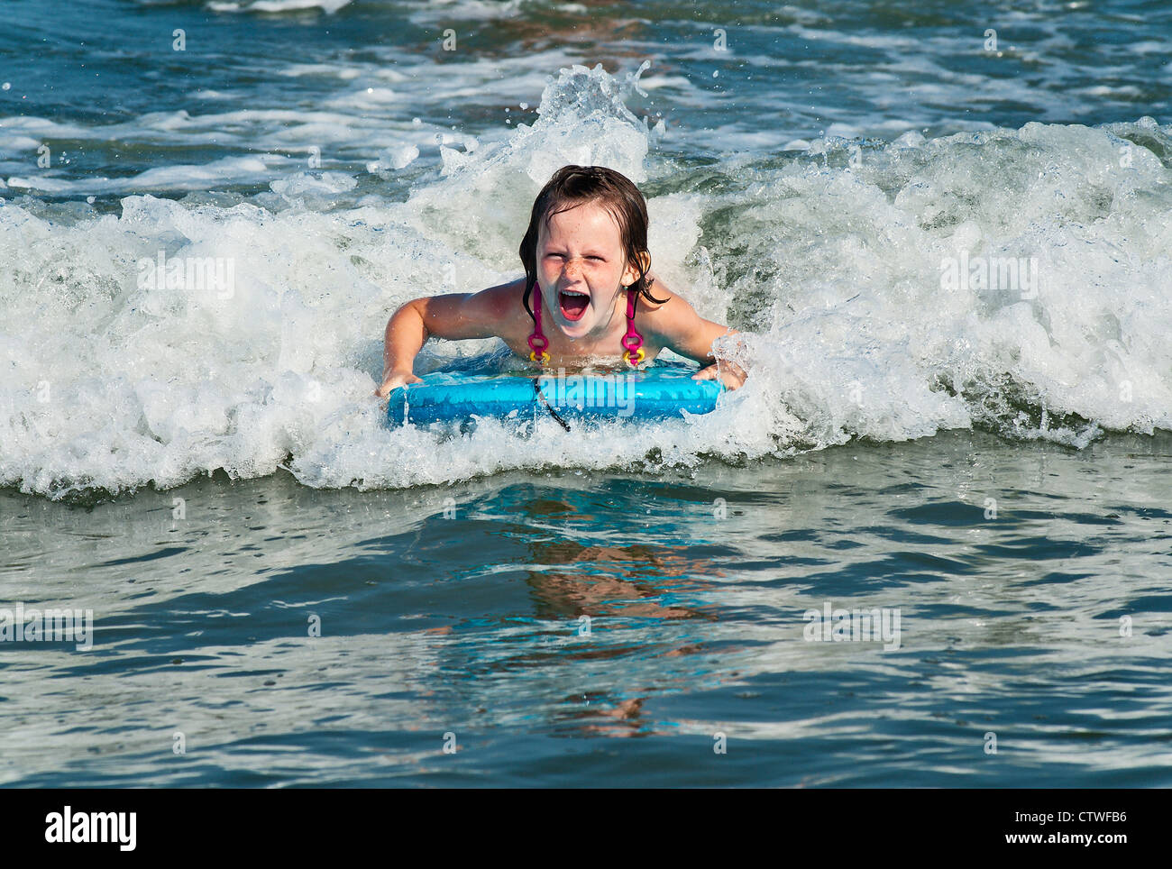 Young girl enjoys the ocean water. - Stock Image
