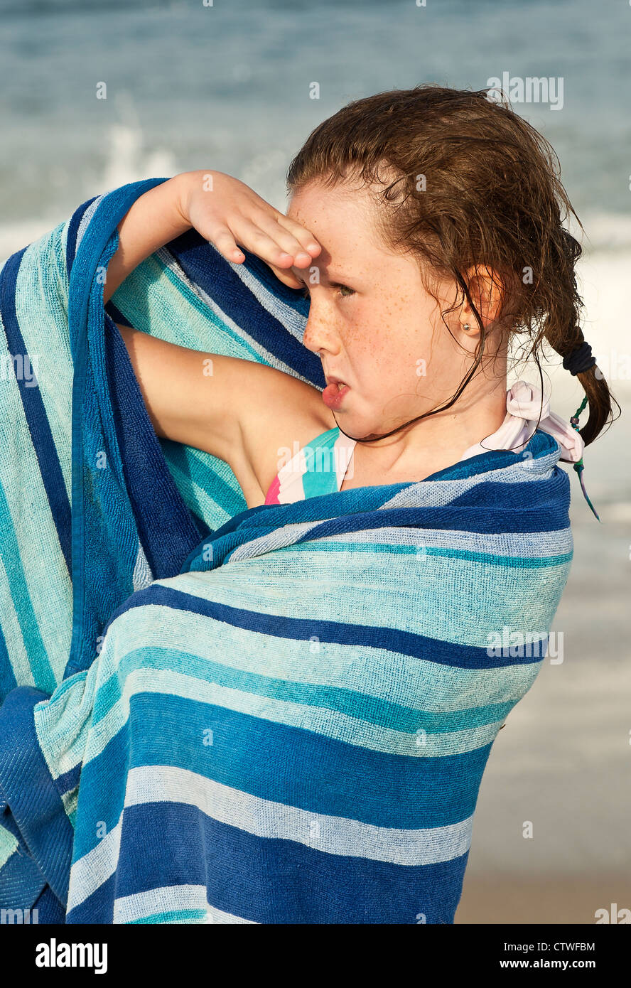 Cute young girl drying off with a beach towel, Cape Cod, MA - Stock Image
