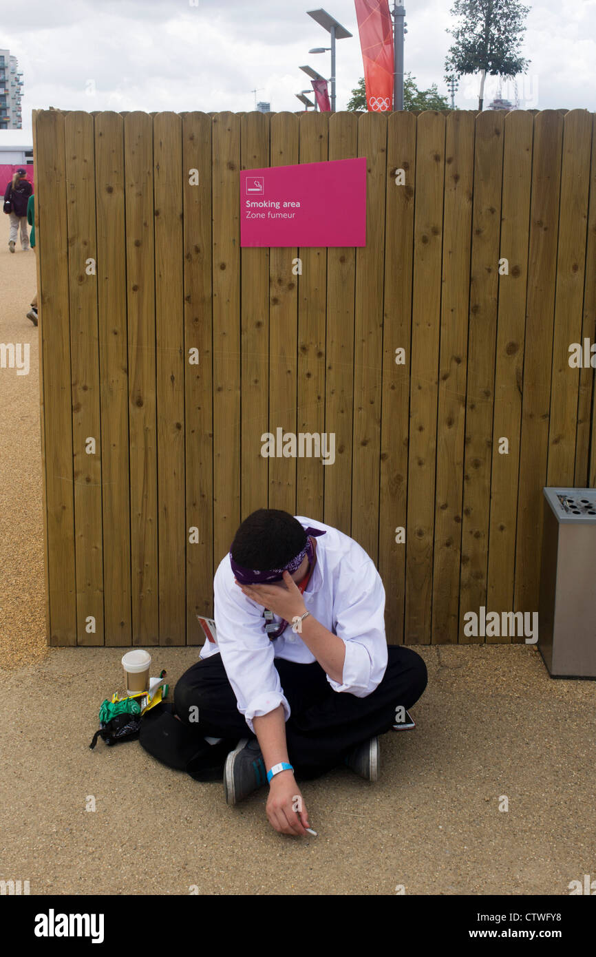 A smoking worker enjoys a rest and cigarette in a designated smoking zone area in the Olympic Park during the London - Stock Image