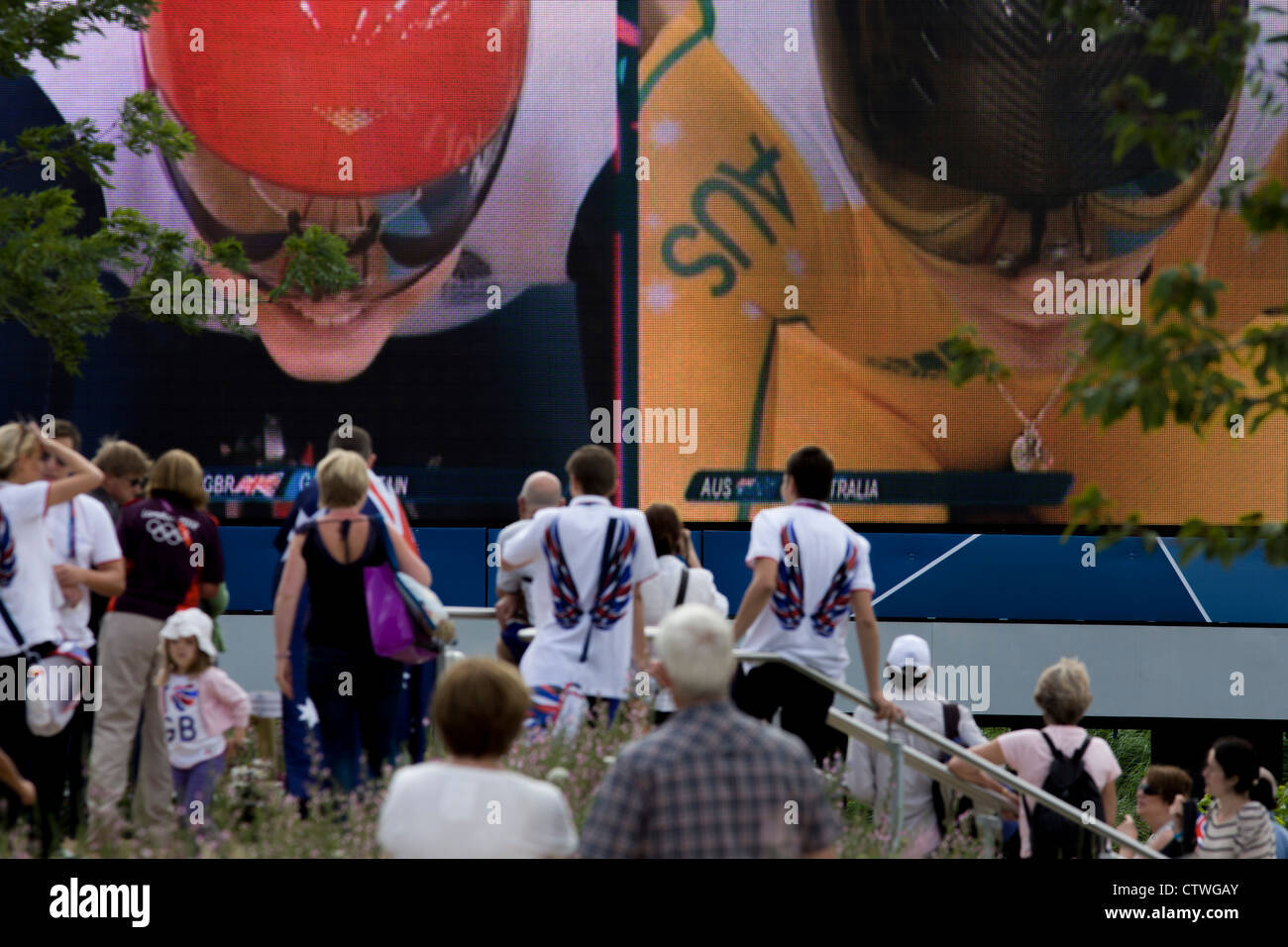 Spectators in the Olympic Park, near the Velodrome, watch a heat of the women's team sprint between Team GB - Stock Image