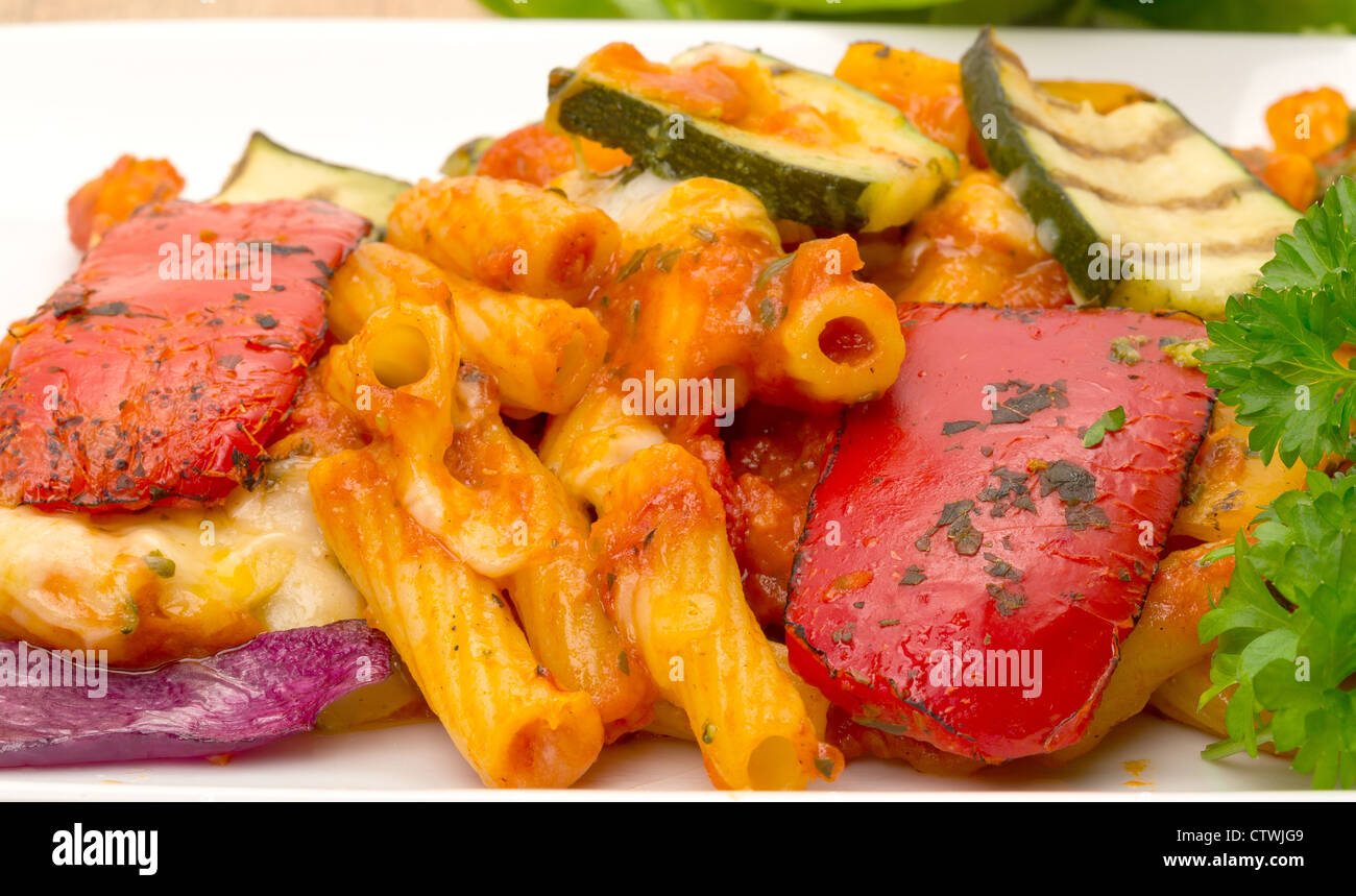 Vegetable pasta bake on a white plate close-up - studio shot - Stock Image