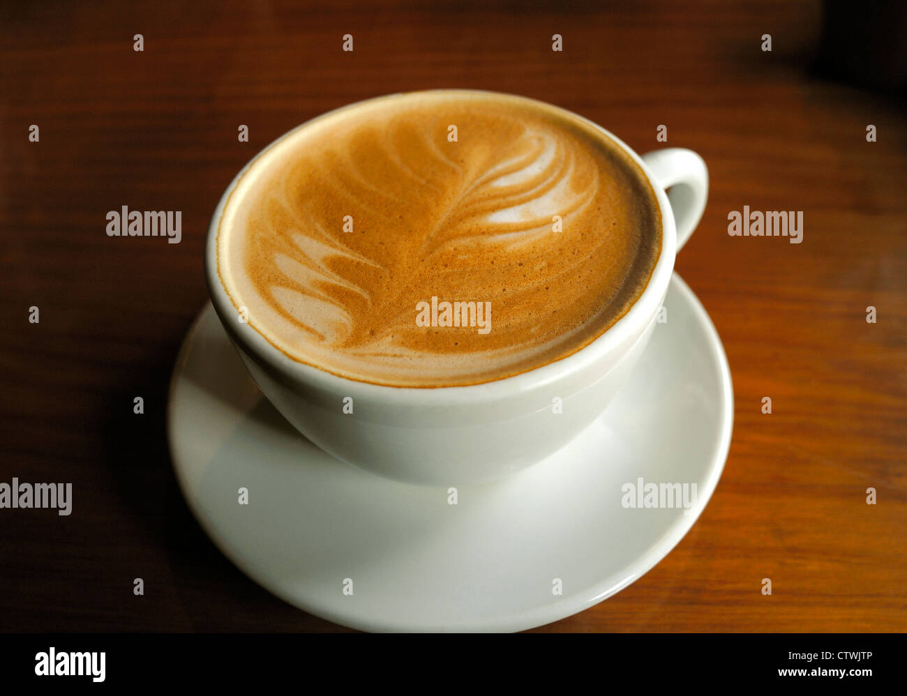 A CUP OF COFFEE , KNOWN IN NEW ZEALAND AS A ' FLAT WHITE '  COMPLETE WITH DESIGN IN THE FROTH COFFEE CUP - Stock Image
