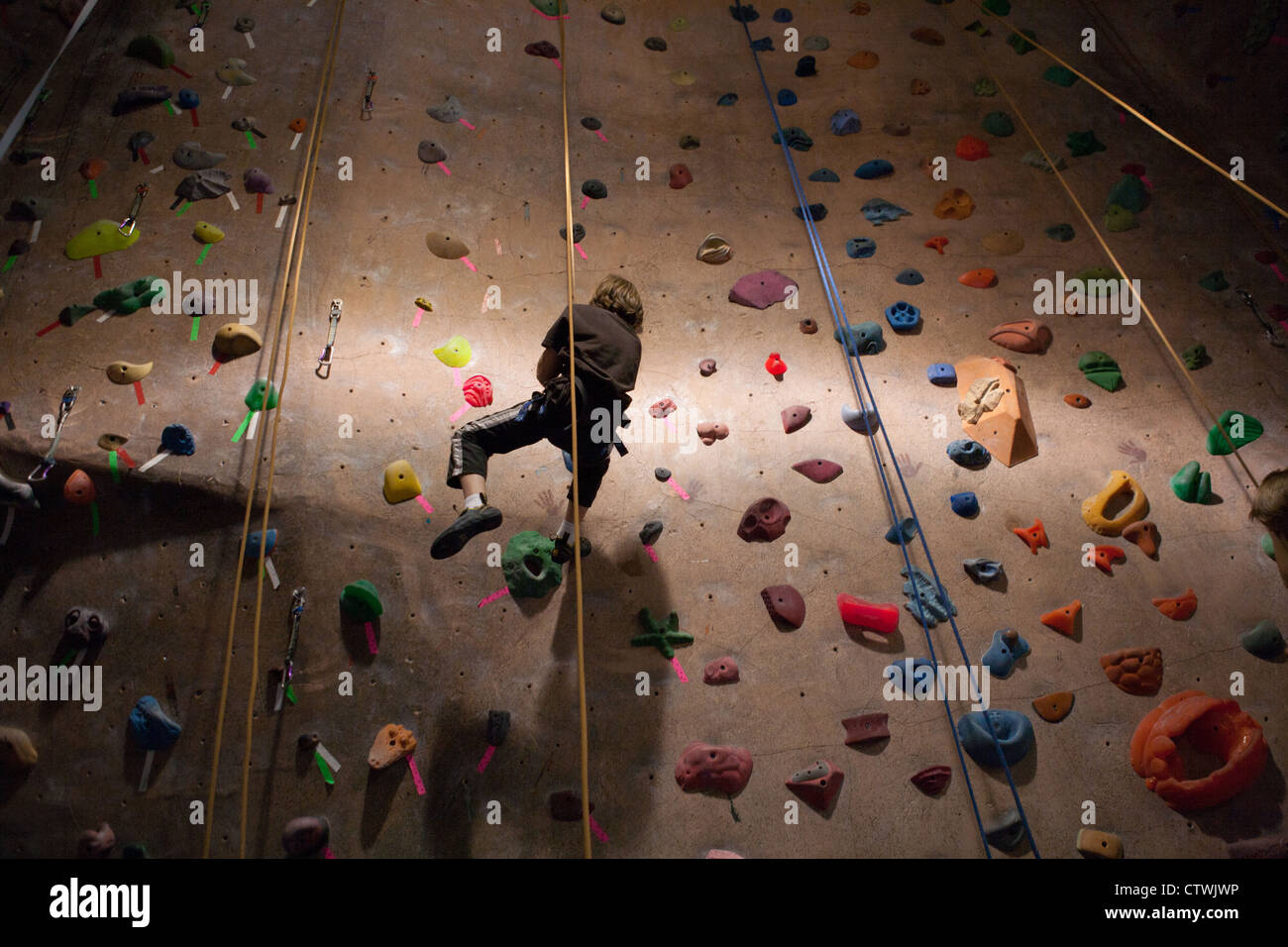 Boy coming down from a climbing wall. - Stock Image