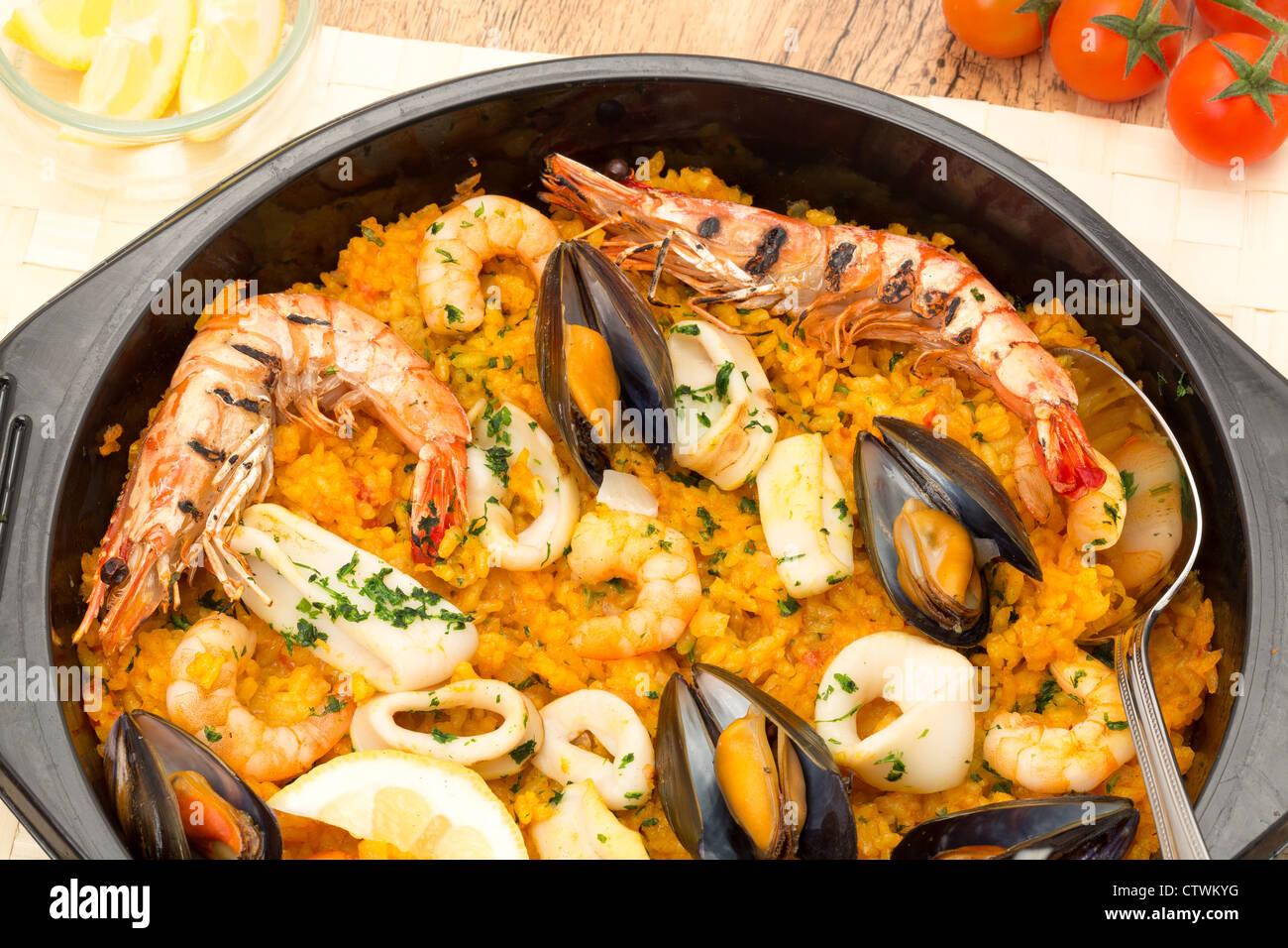 Seafood paella in a black paella pan - Stock Image