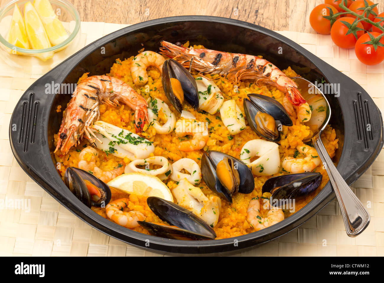 Seafood paella in a black paella serving dish - Stock Image