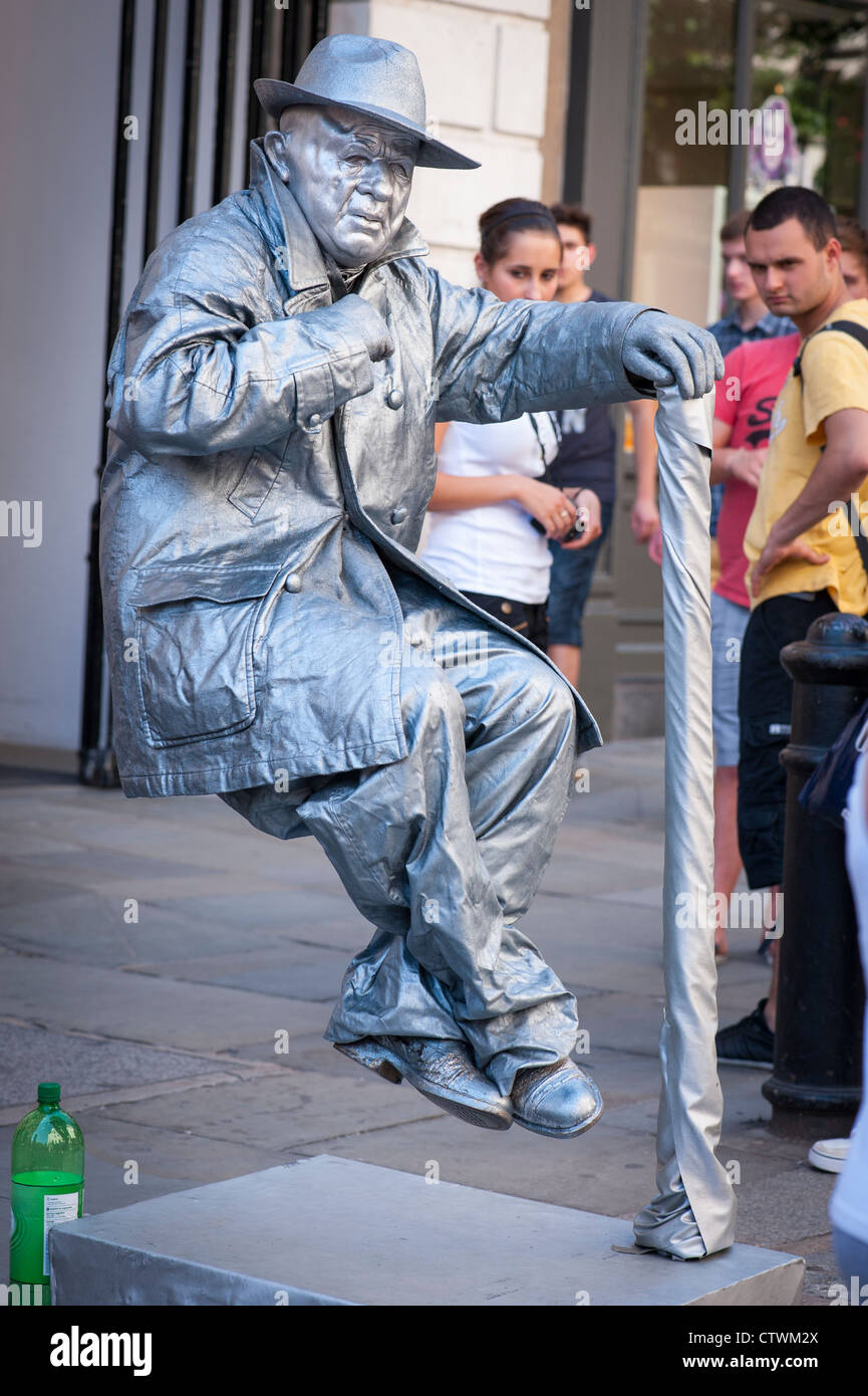 London Covent Gardens Market street entertainer busker mime artist in silver sitting seated on air watched by tourists - Stock Image