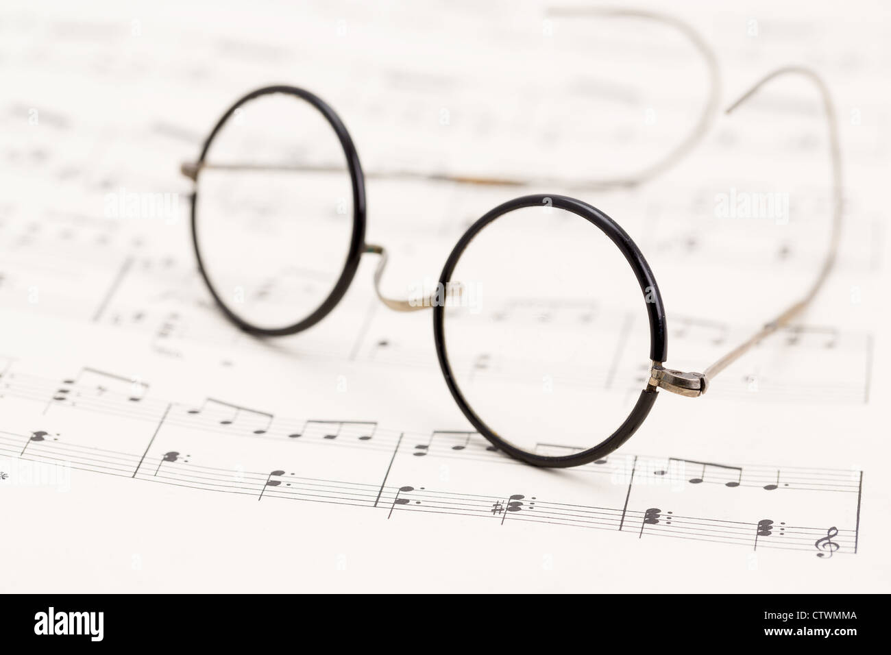 A pair of vintage wire horn rimmed glasses placed onto some sheet music - studio shot with a very shallow depth - Stock Image