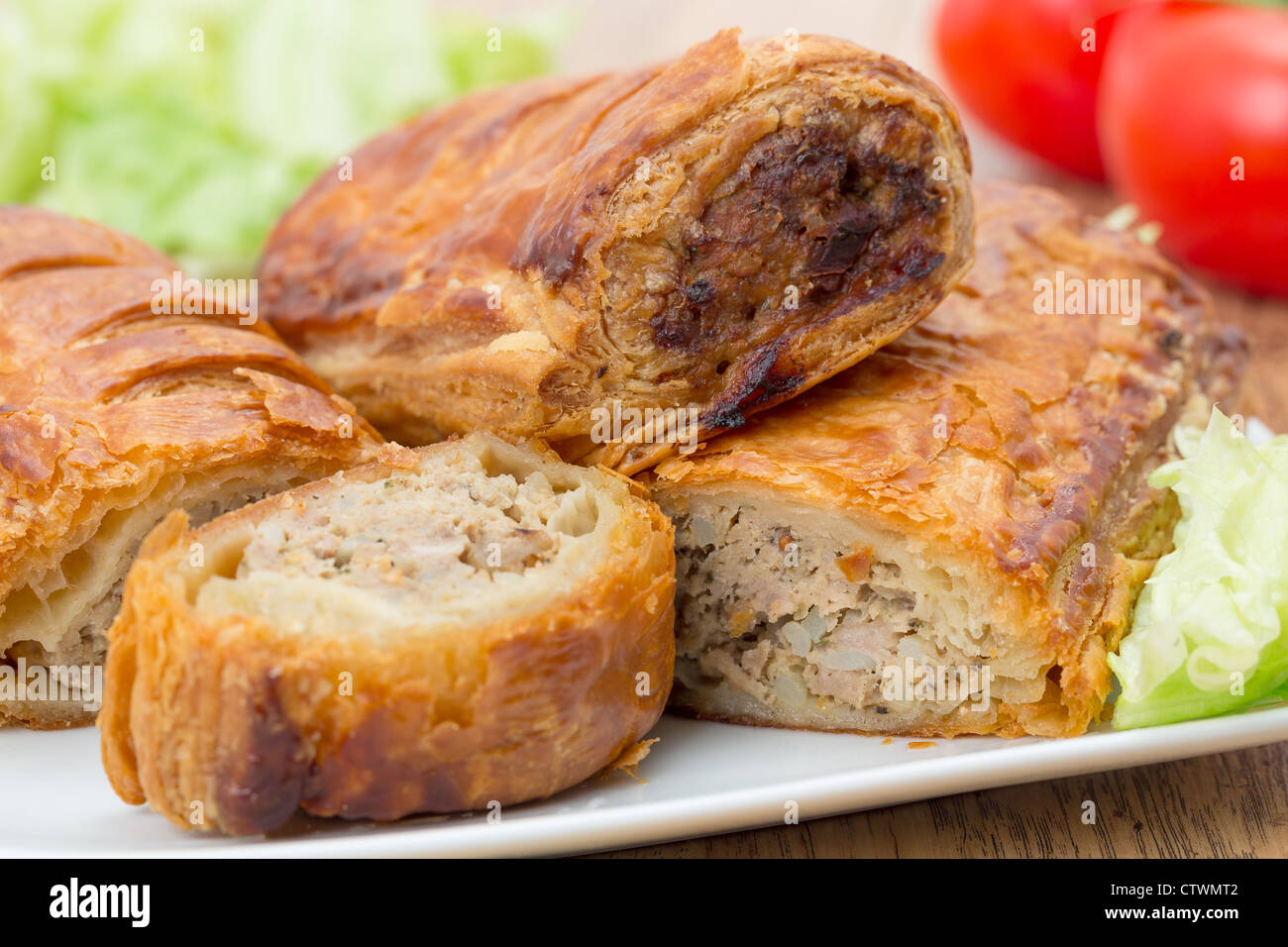 A plate of home made sausage rolls on a white plate - studio shot with a shallow depth of field - Stock Image