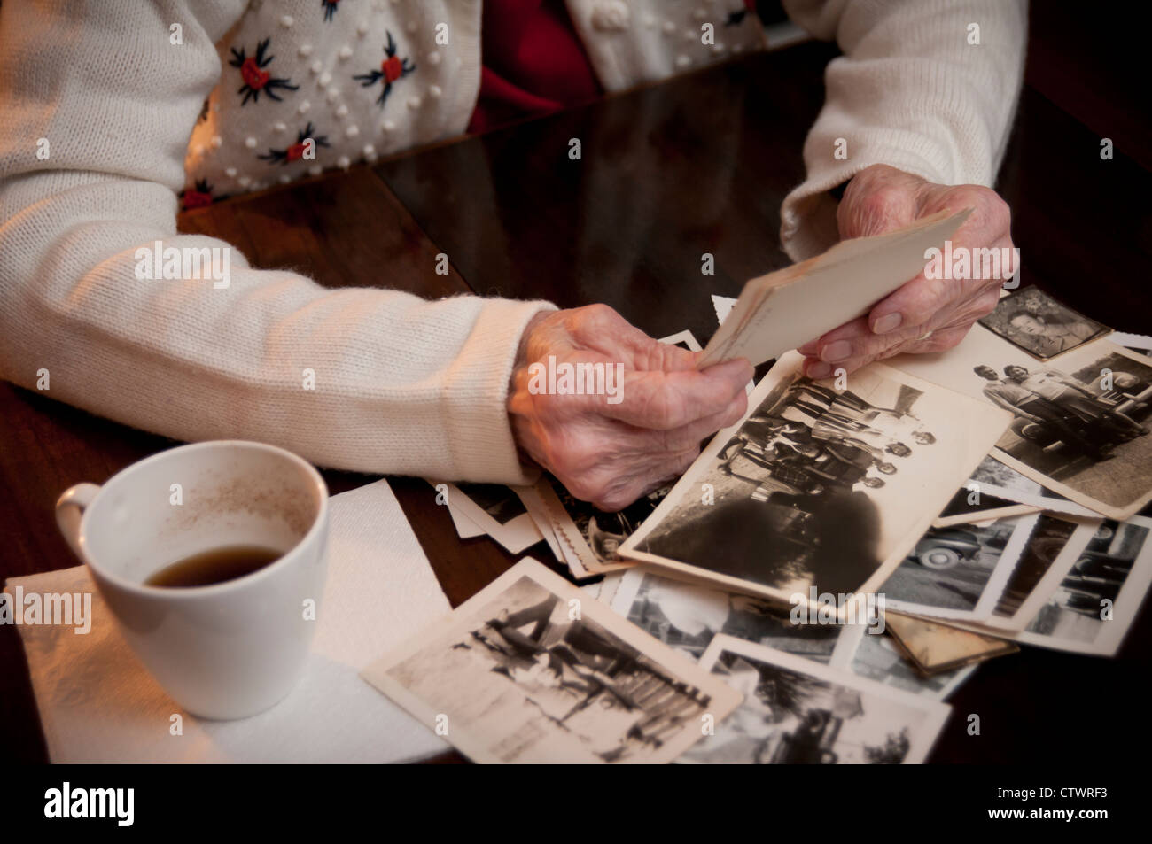 Elderly woman holding an old picture and reminiscing - Stock Image