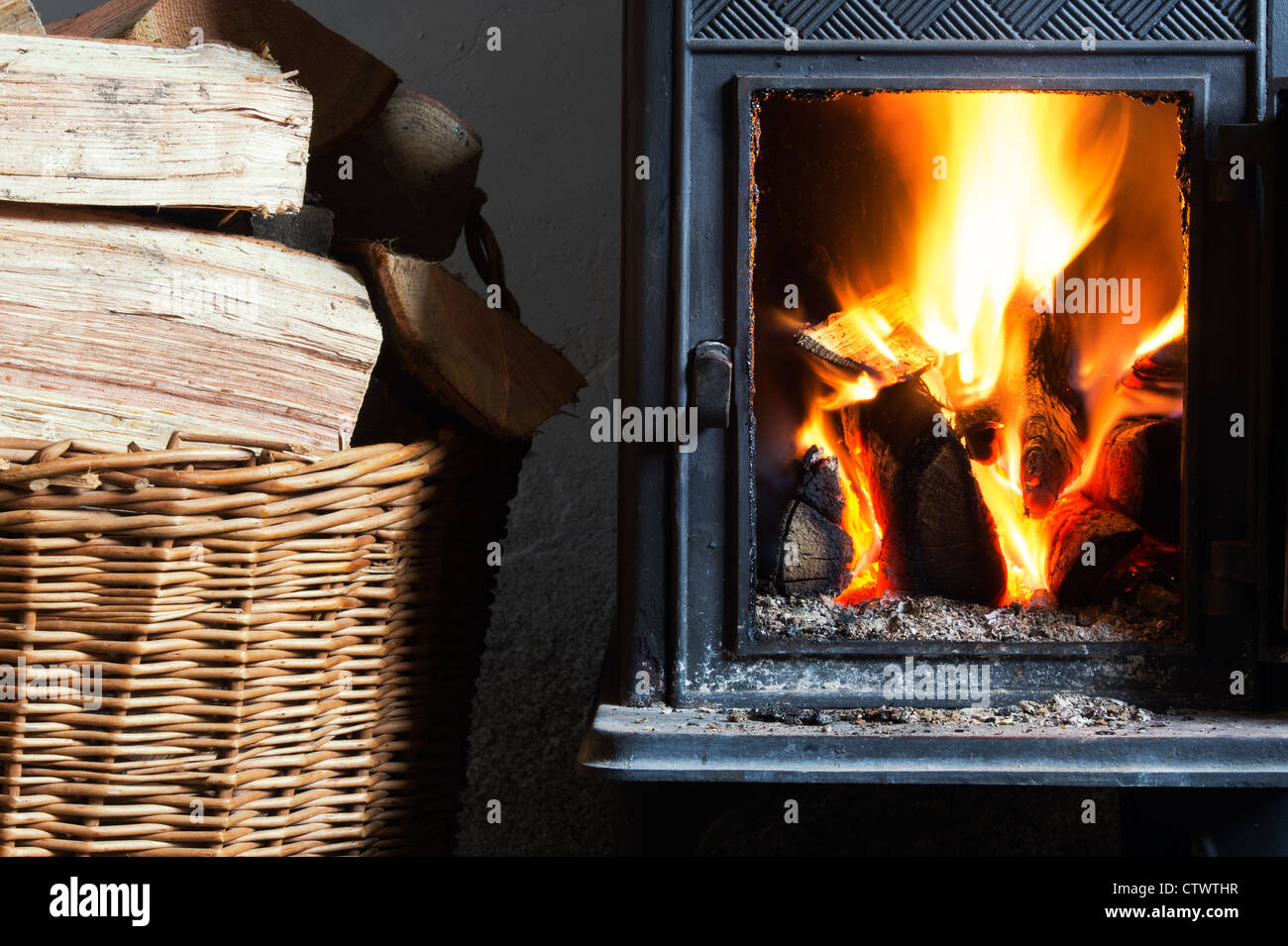 Wood burning in a woodburning stove and a basket of logs. UK Stock Photo