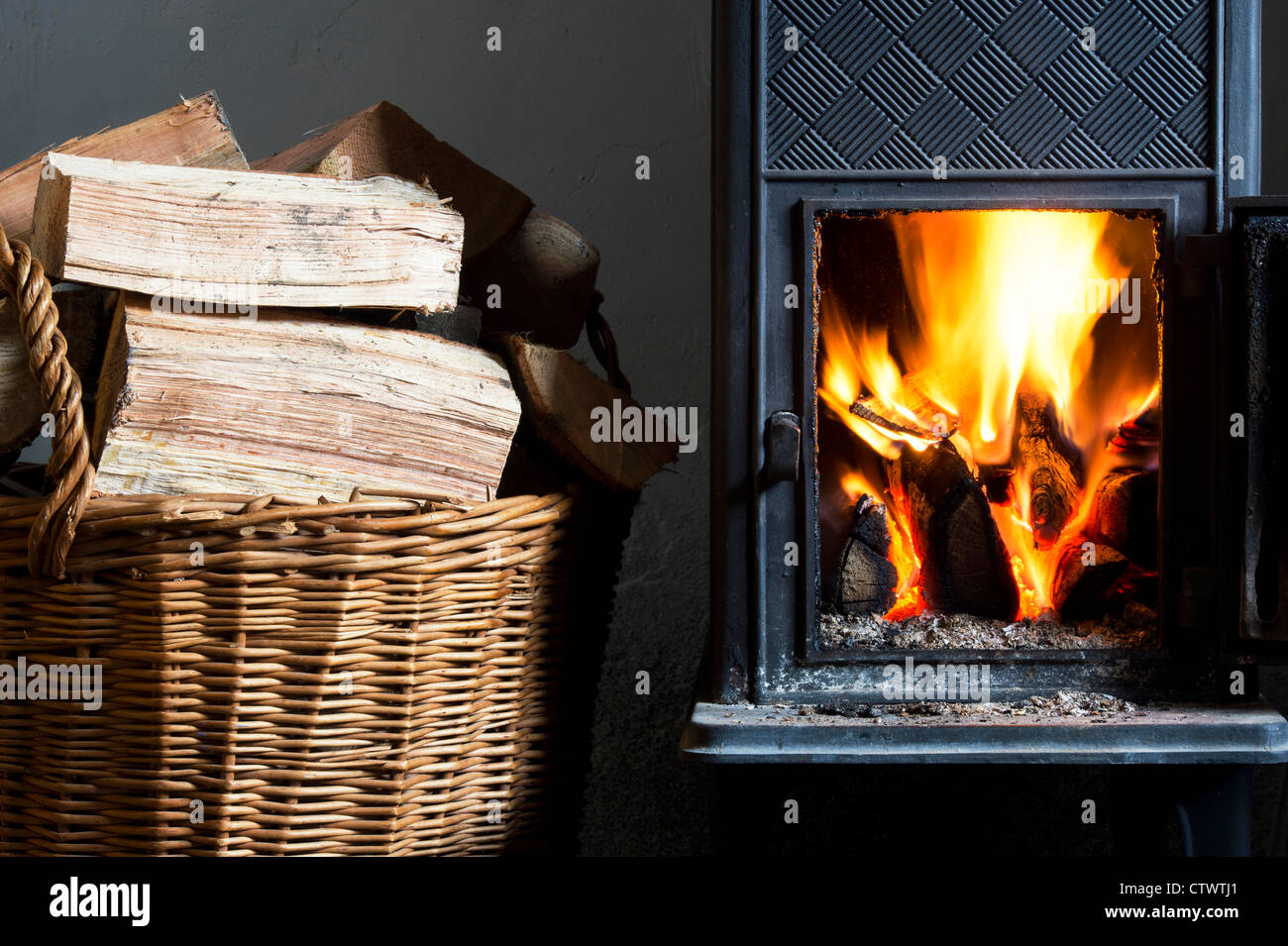 Wood burning in a woodburning stove and a basket of logs. UK - Stock Image