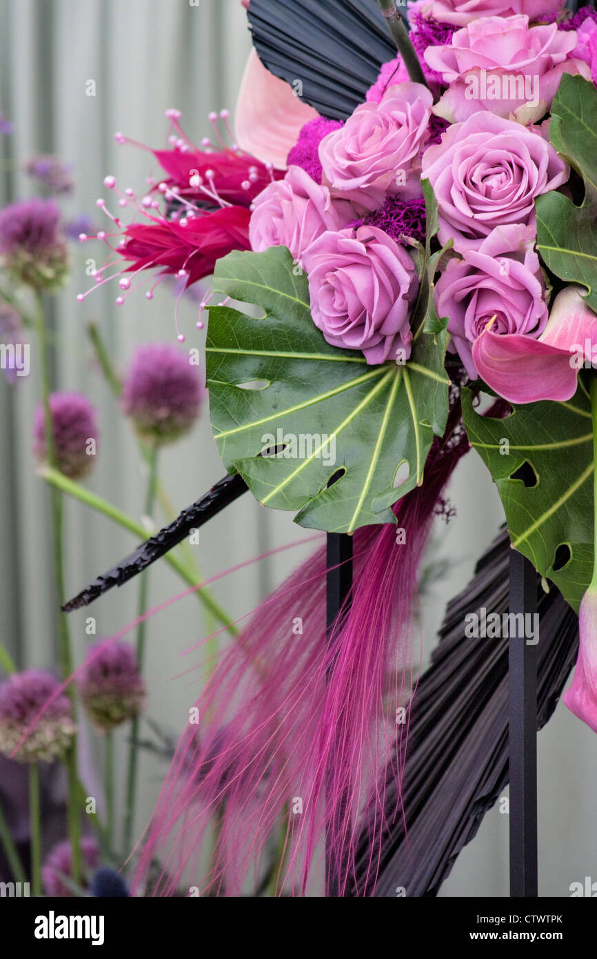a floral display using roses,lilies,alium, monstera leaves and grasses - Stock Image