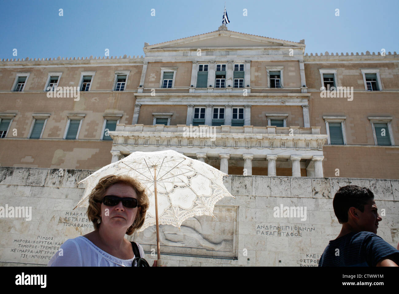 Heat wave in Athens. Tourist protected from the sun with an umbrella in front of Greek Parliament. Syntagma Sq, - Stock Image