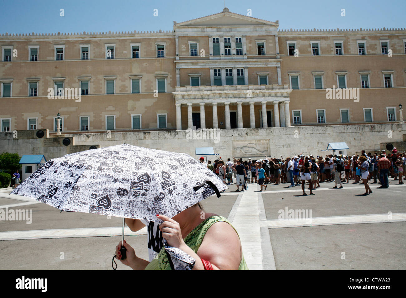 Two women trying to protect themselves from the sun while passing in front of the Greek Parliament. Syntagma Sq, - Stock Image